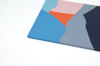 Peinture acrylique réalisée au couteau représentant un paysage onirique en format carré 15 centimètres par 15 centimètres sur carton entoilé. Un poème pictural où les formes et les couleurs remplacent les mots. Ce tableau est composé de diverses formes géométriques suggérant un paysage de montagnes dans les tons assez froids et à tendance plutôt sombres. Rose, orange, gris et différentes nuances de bleu colore ce tableau.