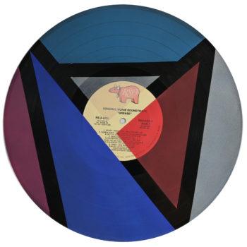 Peinture acrylique sur disque vinyle 33 tours en format 30 centimètres par 30 centimètres. Composition de diverses formes géométriques dans les tons bleus, rouge, argenté et violet. Les aplats de peinture sont séparés par des bandes non peintes qui laissent apparaitre la texture et le noir du vinyle. On peut encore voir le papier initial du disque collé au centre du vinyle, y lire les titres qui sont à certains endroits recouverts de peinture.