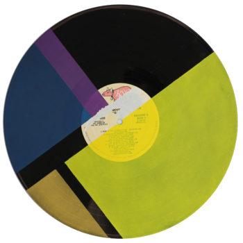 Peinture acrylique sur disque vinyle 33 tours en format 30 par 30 centimètres. Composition de diverses formes géométriques dans les tons bleus, jaune, or et violet. Les aplats de peinture sont séparés par des bandes non peintes qui laissent apparaitre la texture et le noir du vinyle. On peut encore voir le papier initial du disque collé au centre du vinyle, y lire les titres qui sont à certains endroits recouverts de peinture ou en simple transparence.