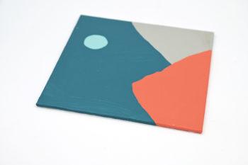 Peinture acrylique réalisée au couteau représentant un paysage onirique en format carré 15 centimètres par 15 centimètres sur carton entoilé. Un poème pictural où les formes et les couleurs remplacent les mots. Ce tableau est composé majoritairement de couleurs froides et une pointe de couleur chaude. On peut distinguer en arrière-plan un ciel dans les tons bleu canard et d'une lune en forme d'ellipse bleu ciel. En premier plan on peut suggérer deux montagnes, l'une orange corail de forme triangulaire sur la gauche et l'autre grise qui s'en va sur la droite.